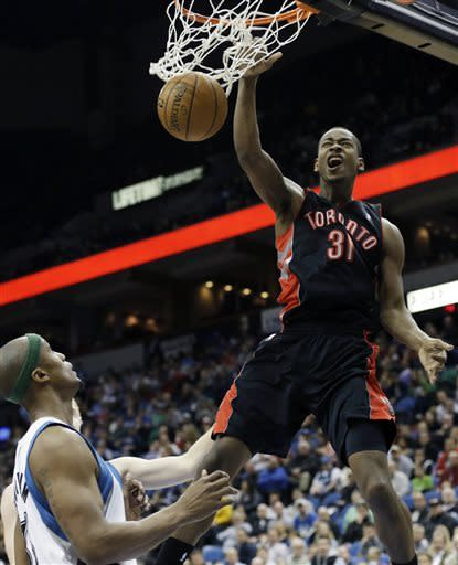 Toronto Raptors' Terrence Ross, right, dunks as Minnesota Timberwolves' Dante Cunningham looks on in the second half of an NBA basketball game, Friday, April 5, 2013, in Minneapolis. The Raptors won 95-93. (AP Photo/Jim Mone)