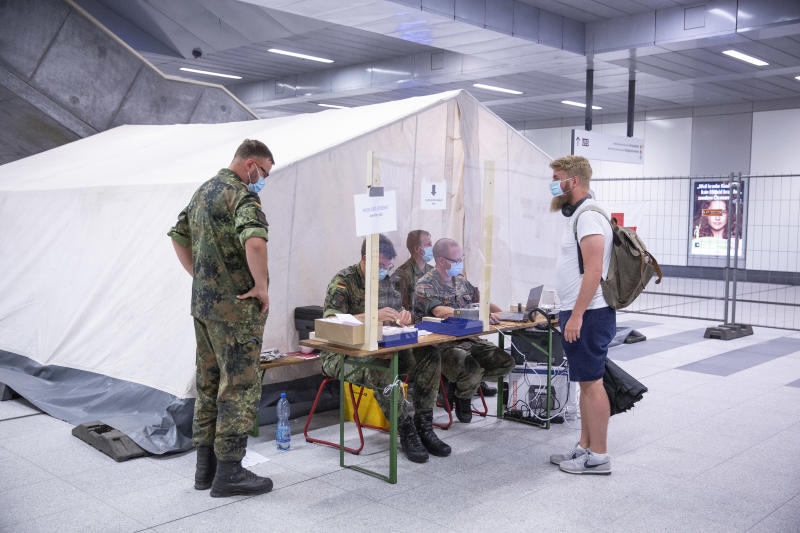 BERLIN, GERMANY - AUGUST 18: Members of the German army collect information from a person at a Covid-19 testing station set up at Berlin main railway station (Hauptbahnhof) during the coronavirus pandemic on August 18, 2020 in Berlin, Germany. German authorities are expanding their testing of travelers arriving from abroad in an effort to stem the spread of the virus. Germany has seen an uptake in infections over the last month, which health authorities attribute to people returning from their holidays in countries that have become coronavirus higher-risk areas. (Photo by Maja Hitij/Getty Images)