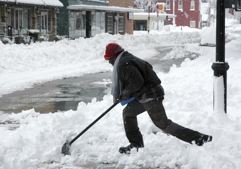 James Smith clears snow from sidewalks Tuesday, Feb. 26, 2013, in downtown Sedalia, Mo., which received about a foot of snow overnight. The second major snowstorm in a week battered the nation's midsection Tuesday, dropping a half-foot or more of snow across Missouri and Kansas with gusting winds blew drifts more than 2 feet high creating treacherous driving conditions for those who dared the morning commute.(AP Photo/The Democrat, Bob Satnan)