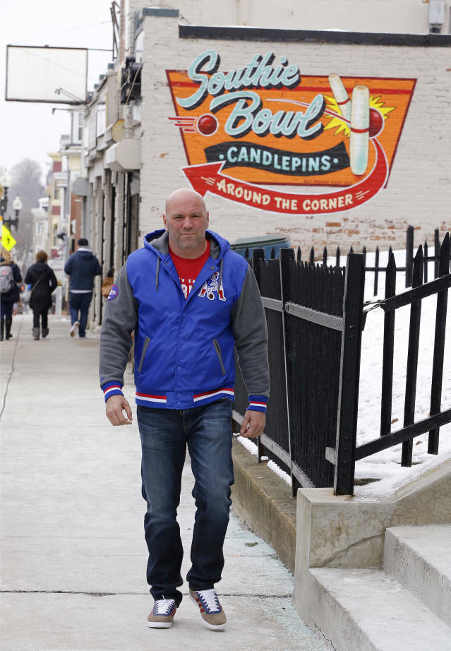"In this Friday, Jan. 19, 2018 photo, Dana White, president of the Ultimate Fighting Championship, the largest mixed martial arts organization in the world, walks along Broadway by the old Courthouse in the ""Southie"" neighborhood of Boston. Long before he ran the UFC White was a ""Southie"" trying to make his way in boxing who dodged the money collectors for notorious crime boss Whitey Bulger that came knocking at his door. (AP Photo/Stephan Savoia)"