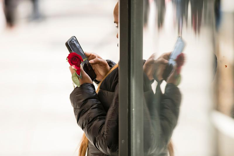 A woman holds a rose as she looks at her phone on Valentine's Day, Thursday, Feb. 14, 2019. (AP Photo/Matt Rourke)