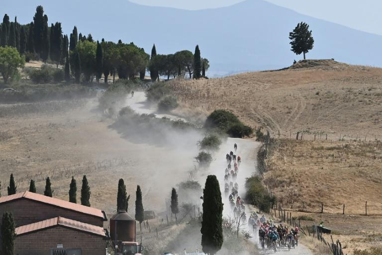 The pack of riders pedal along a dusty gravel road during Saturday's Strade Bianche
