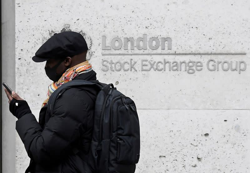 FILE PHOTO: A man wearing a protective face mask walks past the London Stock Exchange Group building in the City of London financial district, whilst British stocks tumble as investors fear that the coronavirus outbreak could stall the global economy, in L