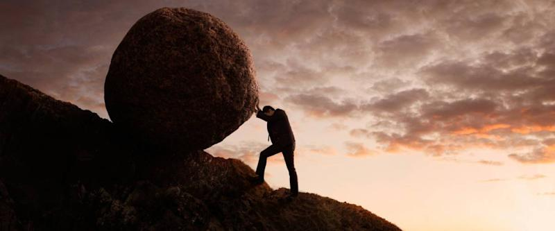 man pushing a boulder up a hill. myth of sisyphus concept.