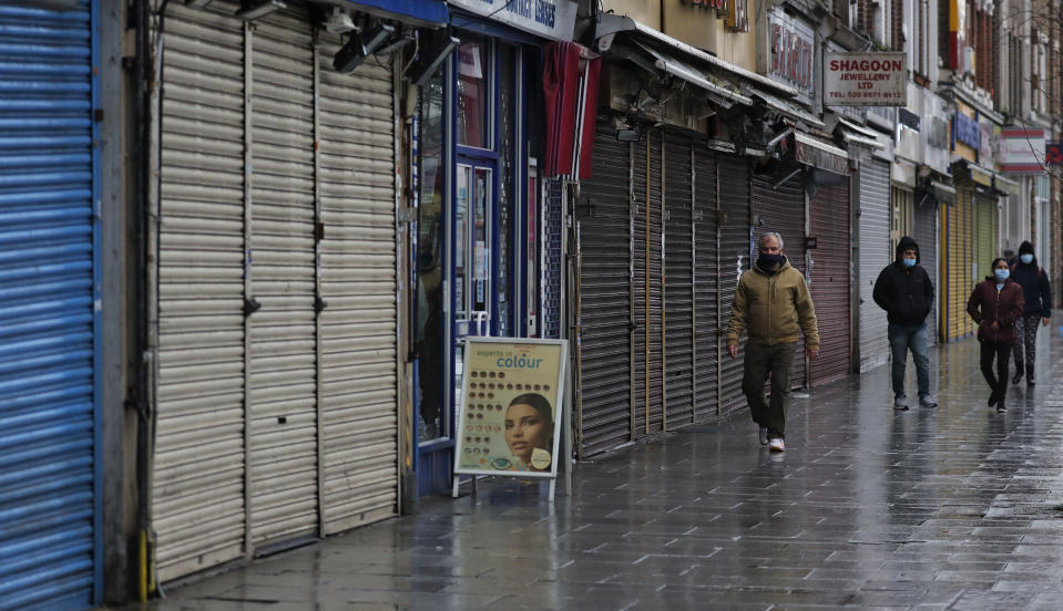 FILE - In this Saturday, Jan. 16, 2021 file photo, people walk past closed shops in London, during England's third national lockdown since the coronavirus outbreak began. Thanks to an efficient vaccine roll out program and high uptake rates, Britain is finally saying goodbye to months of tough lockdown restrictions. From Monday May 17, 2021, all restaurants and bars can fully reopen, as can hotels, cinemas, theatres and museums, and for the first time since March 2020, Britons can hug friends and family and meet up inside other people's houses. (AP Photo/Frank Augstein, File)