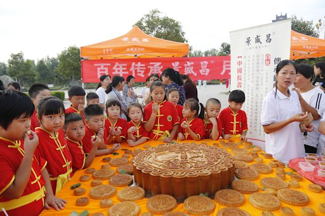 <p>Children eat moon cakes at Xiayi County on September 2, 2018 in Shangqiu, Henan Province of China. A cake shop made a giant moon cake weighing up to 50 kg to welcome Mid-Autumn Festival in Shangqiu on Sunday. (Photo by VCG/VCG via Getty Images) </p>