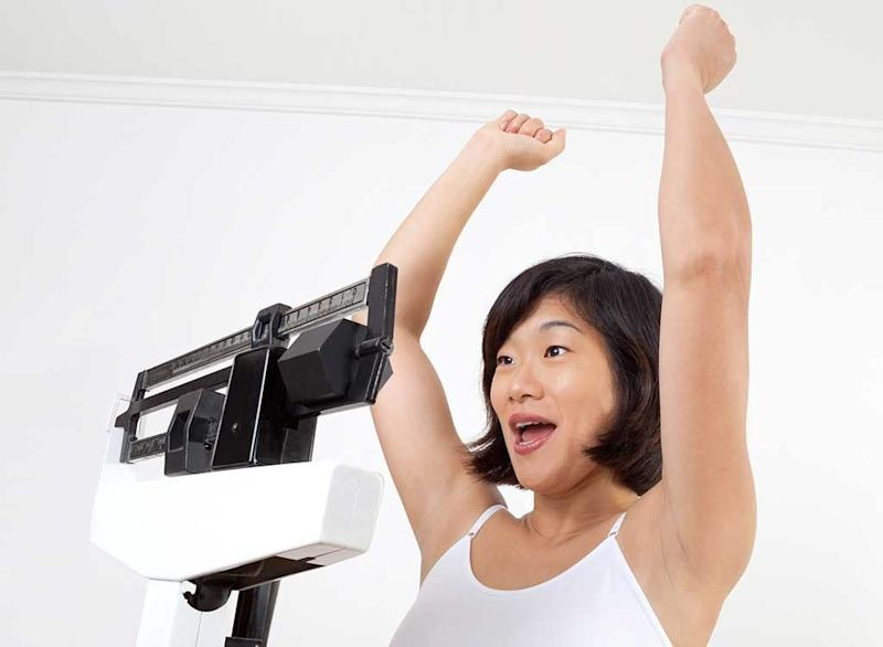 woman weighing on scale success