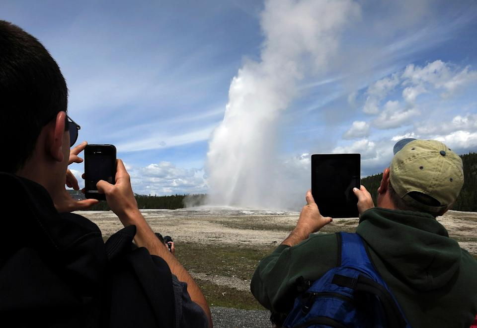 People use phones and tablets to photograph Old Faithful geyser erupting in Yellowstone National Park. The geyser'ssteam can top 300-degrees. (Photo: Jim Urquhart / Reuters)