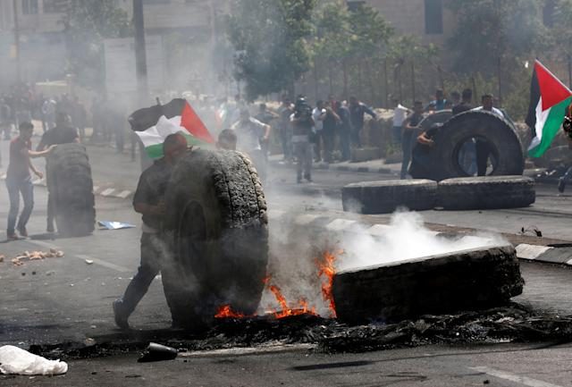 <p>Palestinian protestors burn tires in response to Israeli forces' intervention during a protest, organized to mark 70th anniversary of Nakba, also known as Day of the Catastrophe in 1948, and against United States' plans to relocate the U.S. Embassy from Tel Aviv to Jerusalem in Bethlehem, West Bank on May 15, 2018. (Photo: Wisam Hashlamoun/Anadolu Agency/Getty Images) </p>