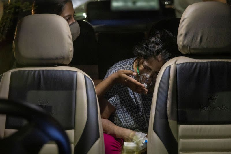 A person with a breathing problem receives oxygen support for free inside her car at a Gurudwara, in Ghaziabad