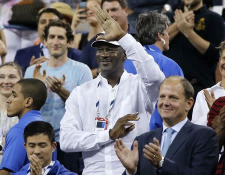 Former basketball great Michael Jordan waves to Roger Federer of Switzerland after Federer defeated Marinko Matosevic of Australia during their men's singles match at the U.S. Open tennis tournament in New York August 26, 2014. REUTERS/Shannon Stapleton