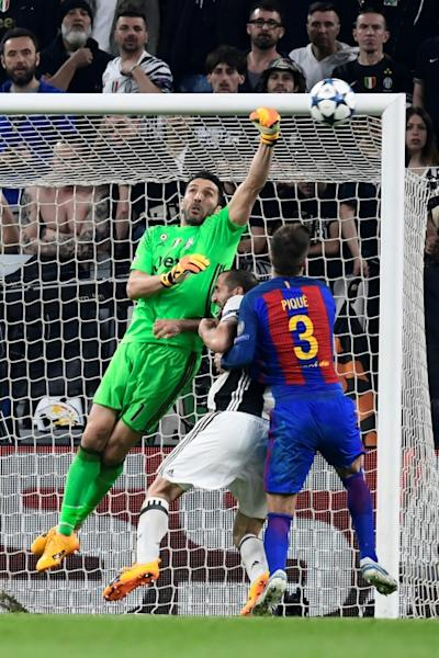 Juventus' goalkeeper Gianluigi Buffon (L) makes a save in front of Juventus' defender Giorgio Chiellini and Barcelona's defender Gerard Pique during the UEFA Champions League quarter final first leg football match on April 11, 2017