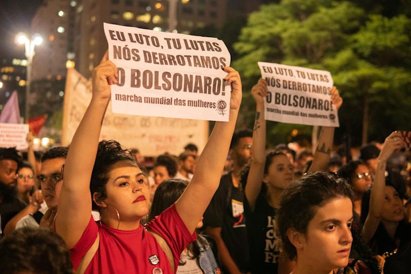 """A woman holds a paper that reads """"I fight, you fight, we defeat Bolsonaro!"""" during a protest in São Paulo, Brazil, October 31, 2019. (Photo: Felipe Beltrame/NurPhoto via Getty Images)"""