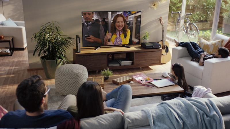 A family sitting in a living room watching television.