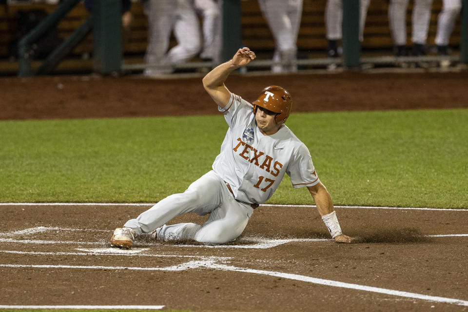 Texas Ivan Melendez (17) slides home in the second inning against Virginia during a baseball game in the College World Series Thursday, June 24, 2021, at TD Ameritrade Park in Omaha, Neb. (AP Photo/John Peterson)