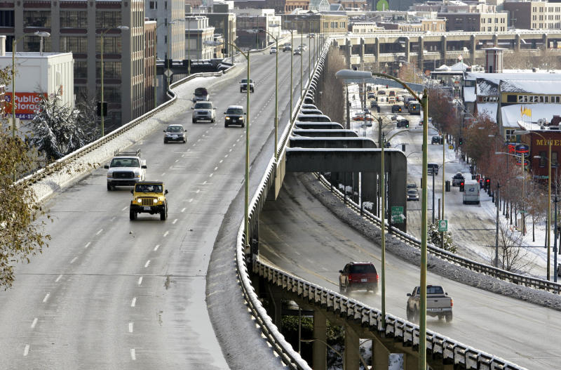 FILE - In this Dec. 23, 2008 file photo, traffic at left heads northbound on the Alaskan Way Viaduct, above the southbound lanes below, through downtown Seattle. New Mayor Mike McGinn is threatening to hold up construction of a massive highway tunnel to replace the waterfront's dilapidated, earthquake-damaged Alaskan Way Viaduct because he fears city taxpayers will be on the hook if costs spiral beyond the $4.2 billion price tag.(AP Photo/Elaine Thompson, File)