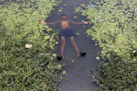 A boy floats in a pond to cool off on a hot summer day on the outskirts of Kolkata, India, April 28, 2016. REUTERS/Rupak De Chowdhuri
