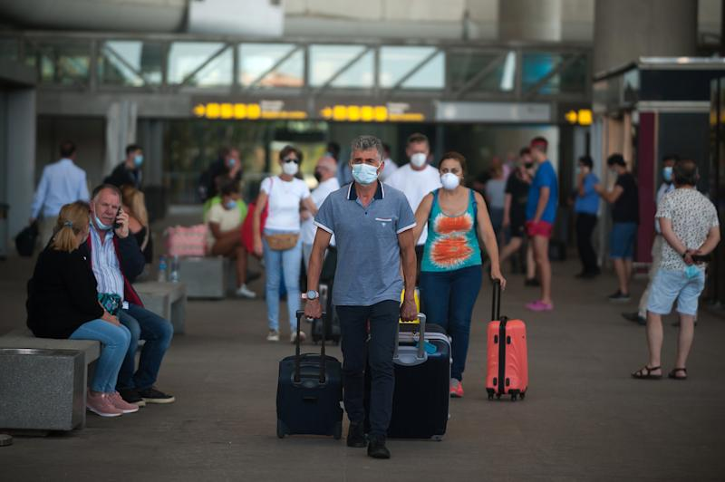 "Passengers wearing face masks walk with their suitcases at Malaga-Costa del Sol airport after the country reopened its borders amid the coronavirus disease (COVID-19) outbreak. Spain has ended the alarm state after more than three months of lockdown. The Spanish government says that from now on people will live under a ""new normality"", using face masks and keeping safe distances during their daily life. (Photo by Jesus Merida / SOPA Images/Sipa USA)"