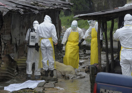 Health workers wearing protective clothing prepare to carry an abandoned dead body presenting with Ebola symptoms at Duwala market in Monrovia, August 17, 2014. REUTERS/2Tango