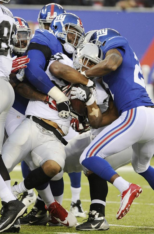 Oakland Raiders running back Rashad Jennings (27) is tackled by New York Giants defenders during the first half of an NFL football game on Sunday, Nov. 10, 2013, in East Rutherford, N.J. (AP Photo/Bill Kostroun)