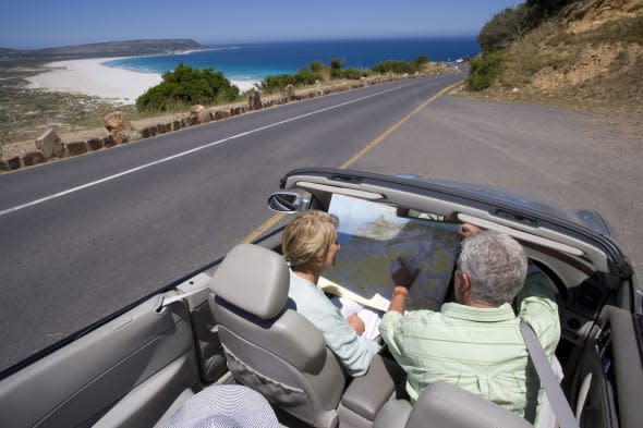 Mature couple looking at map in car