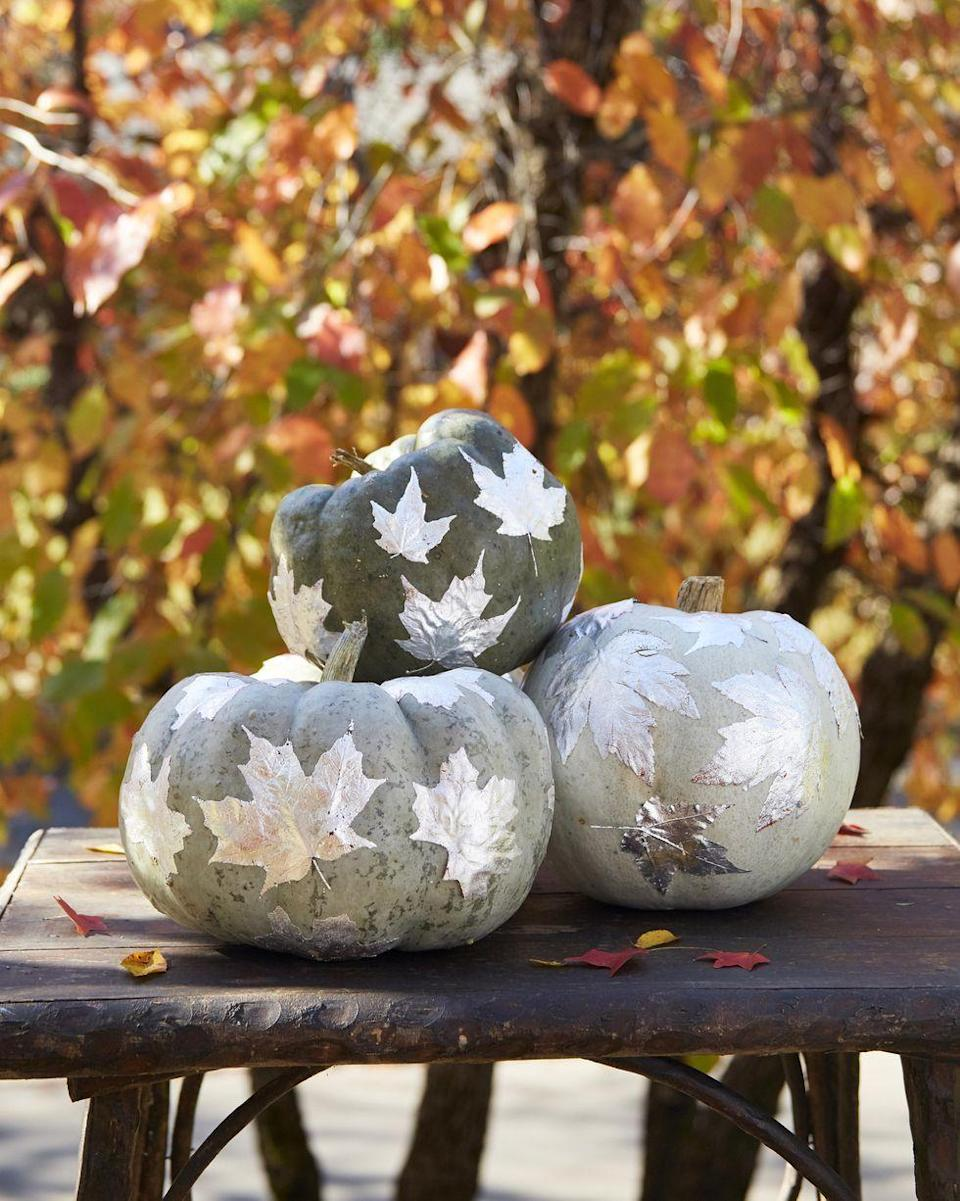 <p>You might think silver is too cold for an autumnal background, but once you see how beautiful these silver leaf pumpkins look on your steps, you'll change your mind. </p><p>Directions: Attach silver leaf with sizing to one side of fake or real leaves (alternatively, you can spray paint leaves silver). Once dry, spray adhesive spray on the back of the leaves and attach to pumpkins. </p>