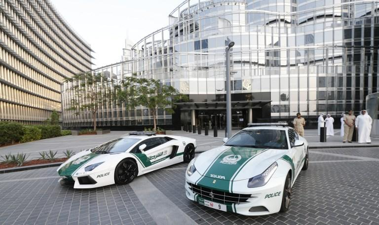 """A picture taken on April 25, 2013 shows Lamborghini and Ferrari police vehicles at the foot of the Burj Khalifa tower  in the Gulf emirate of Dubai. Two weeks after introducing the Lamborghini police car, Dubai Police has introduced a Ferrari to the fleet, to further strengthen the """"image of luxury and prosperity"""" of the emirate. AFP  PHOTO /  KARIM SAHIB"""
