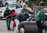 A neighbor is escorted to safety as police surround a home while searching for a suspect in the Boston Marathon bombings in Watertown, Mass., Friday, April 19, 2013. The two suspects in the Boston Marathon bombing killed an MIT police officer and hurled explosives at police in a car chase and gun battle overnight that left one of them dead and his brother on the loose, authorities said Friday. (AP Photo/Charles Krupa)