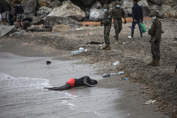 A man lies on the ground as Spanish Army cordon off the area at the border of Morocco and Spain, at the Spanish enclave of Ceuta, on Tuesday, May 18, 2021. Ceuta, a Spanish city of 85,000 in northern Africa, faces a humanitarian crisis after thousands of Moroccans took advantage of relaxed border control in their country to swim or paddle in inflatable boats into European soil. Around 6,000 people had crossed by Tuesday morning since the first arrivals began in the early hours of Monday, including 1,500 who are presumed to be teenagers. (AP Photo/Javier Fergo)
