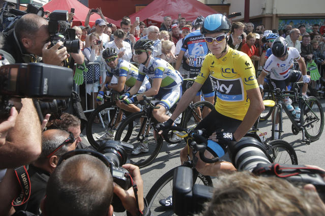 Photographers take picture of Christopher Froome of Britain, wearing the overall leader's yellow jersey, prior to the twelfth stage of the Tour de France cycling race over 218 kilometers (136.2 miles) with start in in Fougeres and finish in Tours, western France, Thursday July 11 2013. (AP Photo/Christophe Ena)