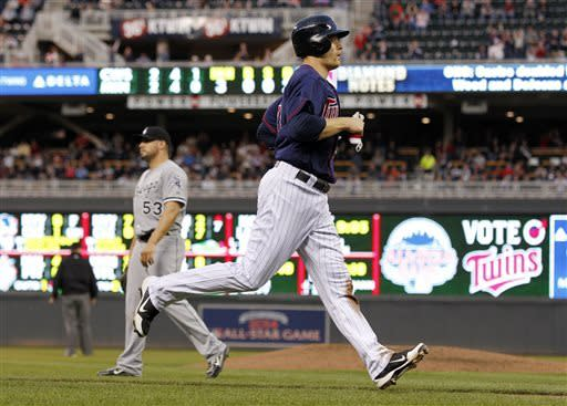 Minnesota Twins' Justin Morneau scores on Trevor Plouffe's two-run double against Chicago White Sox starting pitcher Hector Santiago, left, during the third inning of a baseball game, Monday, May 13, 2013, in Minneapolis. (AP Photo/Genevieve Ross)
