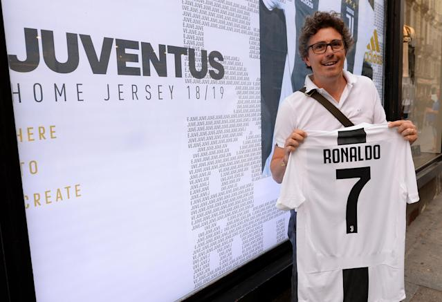 A Juventus supporter holds, after buying, the first original Juventus' jersey printed with the name and number of Cristiano Ronaldo after his transfer to Juventus in Turin, Italy July 10, 2018. REUTERS/Massimo Pinca