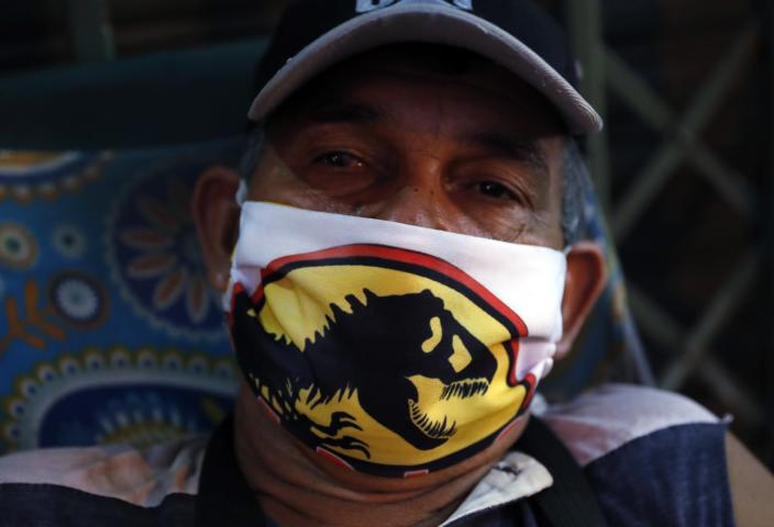 Night guard Felix Ortiz wears a mask with the logo of Jurassic World as he poses for a photo in front of a closed store at Market 4 during a lockdown and the spread of the new coronavirus, in Asuncion, Paraguay, Thursday, April 30, 2020. Ortiz also sells masks like the one he is wearing. (AP Photo/Jorge Saenz)