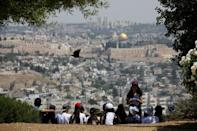 A crow flies past as Jewish school children gather at a look-out point on the Armon Hanatziv Promenade in Jerusalem May 11, 2017. Picture taken May 11, 2017. REUTERS/Amir Cohen