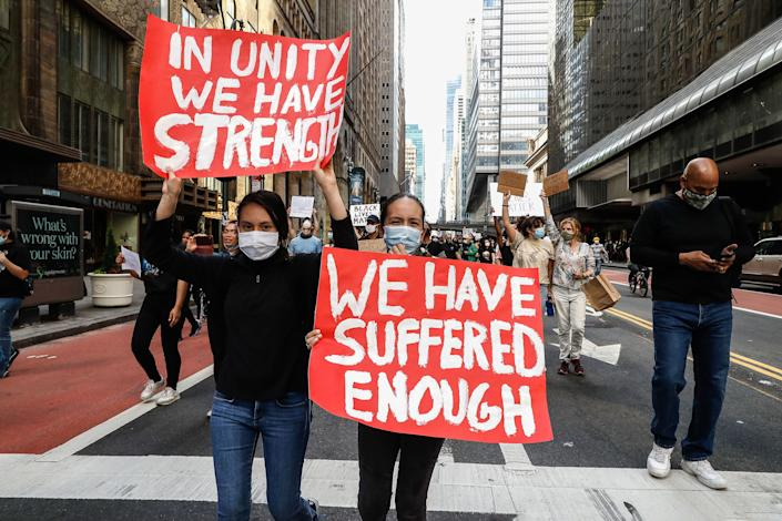"""<i>New York protesters take part in a June 1 demonstration in response to the death of George Floyd. The sign on the left reads: """"In unity we have strength;"""" the one on the right reads: """"We have suffered enough."""" </i>"""
