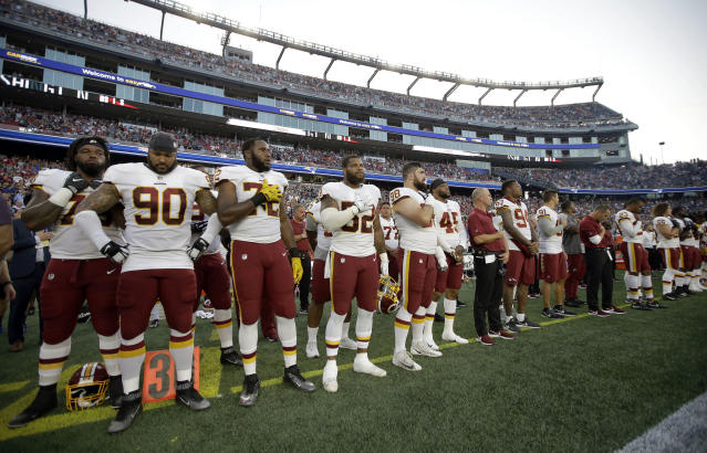 Washington Redskins players stand for the national anthem before a preseason NFL football game against the New England Patriots, Thursday, Aug. 9, 2018, in Foxborough, Mass. (AP Photo/Steven Senne)