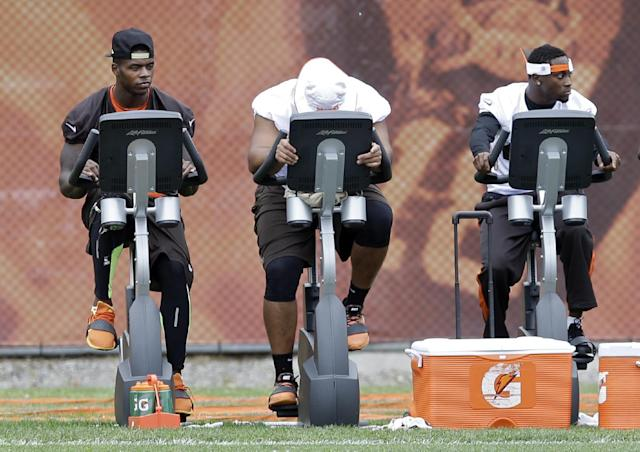 Cleveland Browns wide receiver Josh Gordon, left, rides a stationary bike during a mandatory minicamp practice at the NFL football team's facility in Berea, Ohio Wednesday, June 11, 2014. The Browns are awaiting word from the NFL on a possible suspension of their star receiver for violating the league's substance abuse policies. (AP Photo/Mark Duncan)
