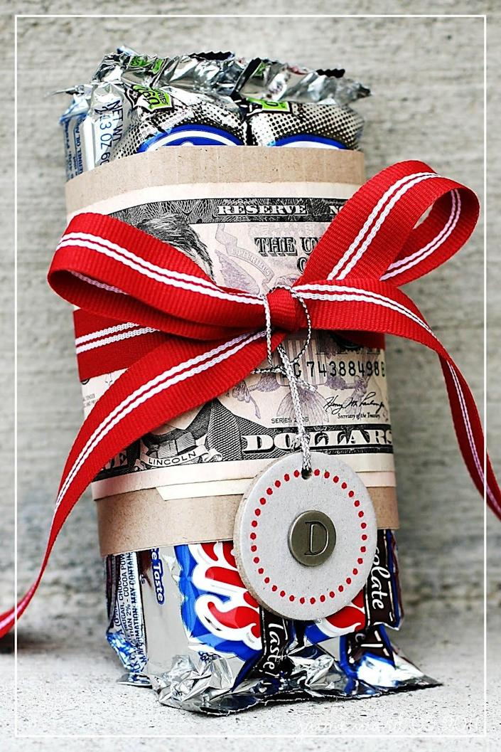 """<p>Add a little weight to your package by wrapping a bill around some candy bars. This is the real """"fun size."""" As an extra touch, why not use 100 Grand bars instead of 3 Musketeers? <i>(Photo: <a href=""""http://simplyjstudio.blogspot.com/2011/06/quick-gifts.html"""" rel=""""nofollow noopener"""" target=""""_blank"""" data-ylk=""""slk:Simply J Studio)"""" class=""""link rapid-noclick-resp"""">Simply J Studio)</a></i></p>"""