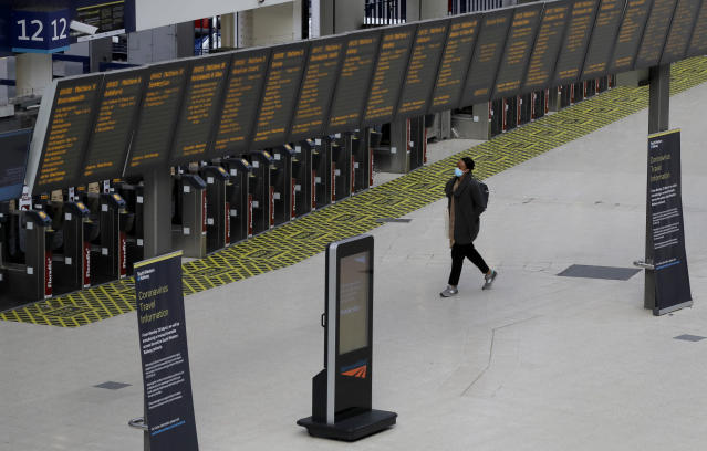 A traveler walks through a quiet Waterloo Station in London during rush hour, Wednesday, May 13, 2020, as the country continues in lockdown to help stop the spread of coronavirus. Some of the coronavirus lockdown measures are being relaxed in England on Wednesday, with those workers who are unable to work from home, such as those in construction and manufacturing, encouraged to return to work. (AP Photo/Kirsty Wigglesworth)