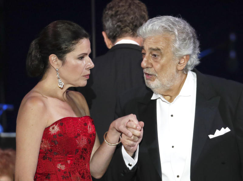 """FILE - In this file photo taken on Aug. 28, 2019, Opera star Placido Domingo holds the hand of Ana Maria Martinez at the end of a concert in Szeged, Hungary. The 78-year-old singer who rose to stardom as a tenor has been confirmed to sing the baritone title role in """"Nabucco"""" at the Zurich Opera House this Sunday. It will be his first time performing since stepping down Oct. 2 as general director of the Los Angeles Opera and withdrawing from future performances at the company. (AP Photo/Laszlo Balogh)"""