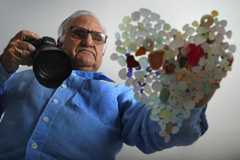 Donald Verger arranges sea glass in the shape of a heart, Thursday, Feb. 11, 2021, in Falmouth, Maine. After photographing his art, Verger donates photos and cards to schools and hospitals as a way of giving back during the pandemic. (AP Photo/Robert F. Bukaty)