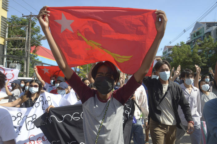 Anti-coup protesters display a party flag of the National League for Democracy (NLD) during a demonstration in Yangon, Myanmar, Friday, May 14, 2021. (AP Photo)
