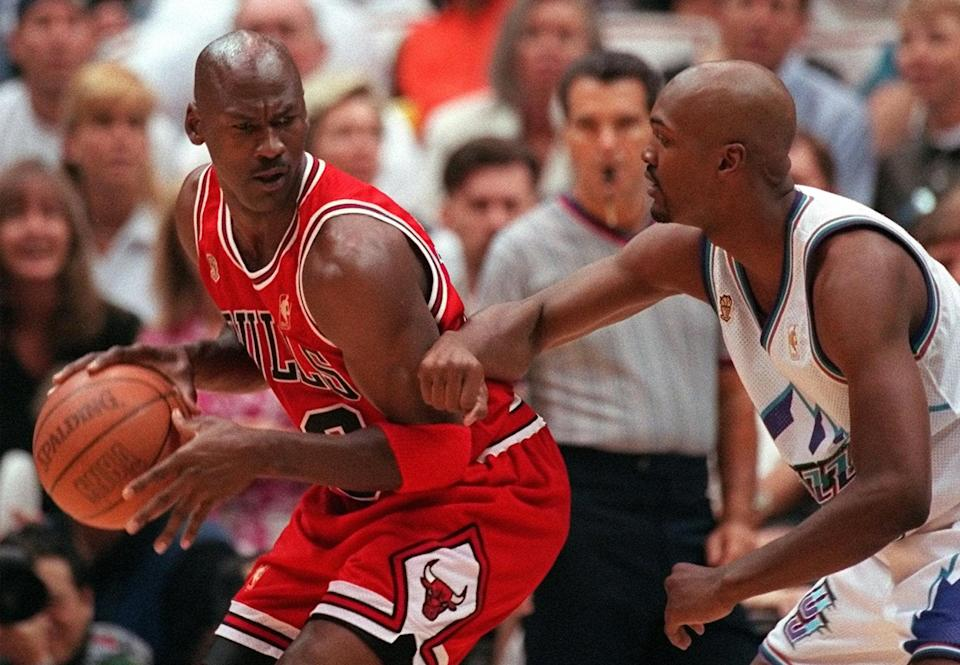 Chicago Bulls' Michael Jordan scowls over his shoulder as he is guarded closely by Utah Jazz's Bryon Russell during the first quarter of Game 4 in the NBA Finals on Sunday, June 8, 1997, in Salt Lake City. (AP Photo/Douglas C. Pizac)