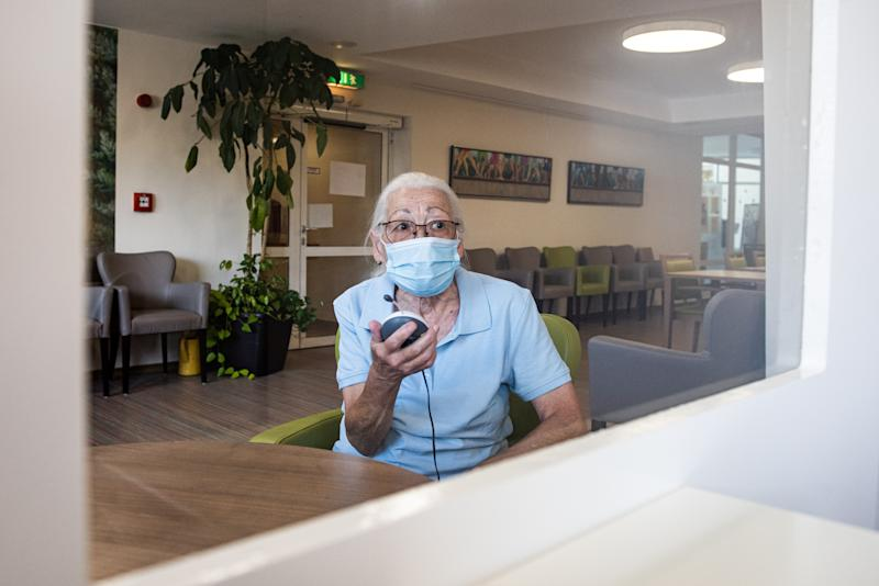 """26 June 2020, Hessen, Kassel: Resident Jenny Nelle talks to a visitor via a baby monitor and through a Plexiglas panel in the entrance area of the AWO senior citizens' centre """"Käthe-Richter-Haus"""". Since one week residents of old people's and nursing homes are allowed to have more visitors again. (to dpa """"More visitors in homes: blessing and risk factor"""") Photo: Swen Pförtner/dpa (Photo by Swen Pförtner/picture alliance via Getty Images)"""