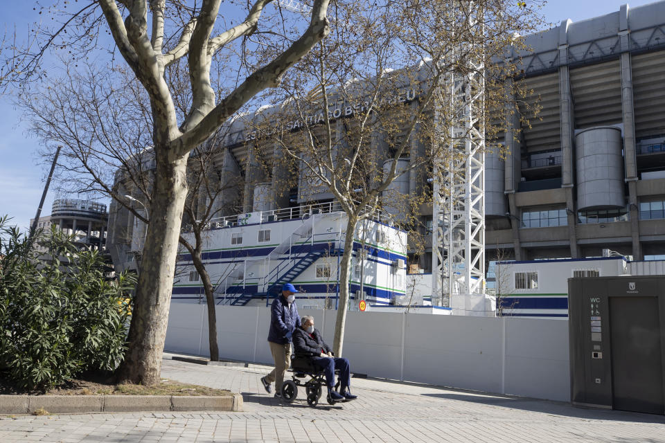 A man is pushed in the wheelchair while wearing protective masks near Real Madrid's Santiago Bernabeu stadium in Madrid, Spain, Friday, March 13, 2020. Real Madrid have said its players were being placed in isolation after one of the club's basketball players, who share facilities with Madrid's soccer players, tested positive for the COVID-19 coronavirus. That led to the instant decision by the Spanish league to bring matches to a halt for the next two rounds. For most people, the new coronavirus causes only mild or moderate symptoms. For some it can cause more severe illness, especially in older adults and people with existing health problems. (AP Photo/Paul White)