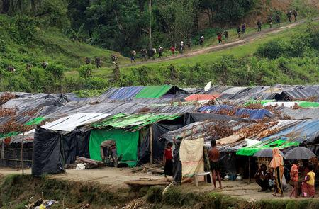 Rohingya refugees stand outside their temporary shelters at no man's land between Bangladesh-Myanmar border, as Myanmar security forces walk past a fence in Maungdaw