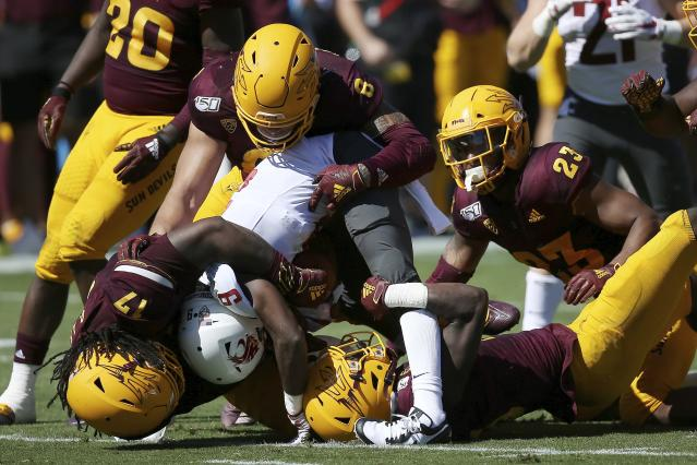 Washington State wide receiver Renard Bell (9) is tackled by Arizona State defensive lineman George Lea (17), linebacker Merlin Robertson (8), linebacker Tyler Whiley (23) and safety Cam Phillips, bottom, during the first half of an NCAA college football game Saturday, Oct. 12, 2019, in Tempe, Ariz. (AP Photo/Ross D. Franklin)