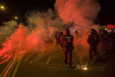 Policemen walk between flares thrown by right wing protesters who are against bringing asylum seekers to an accomodation facility in Heidenau, Germany August 22, 2015. REUTERS/Axel Schmidt