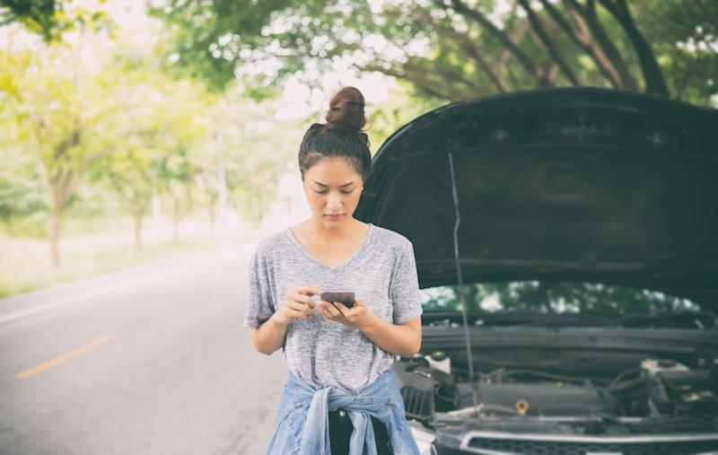 Woman using mobile phone while looking and Stressed man sitting after a car breakdown on street