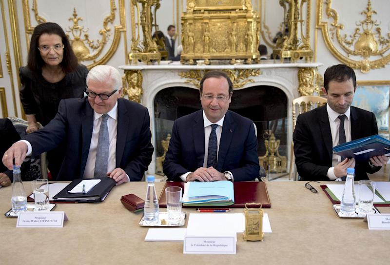 German Foreign Minister Frank-Walter Steinmeier, second left, sits next to French President Francois Hollande, center, and French Education Minister Benoit Hamon, right, during the weekly cabinet meeting at the Elysee palace, Wednesday May 14, 2014, in Paris. (AP Photo/Alain Jocard, Pool)